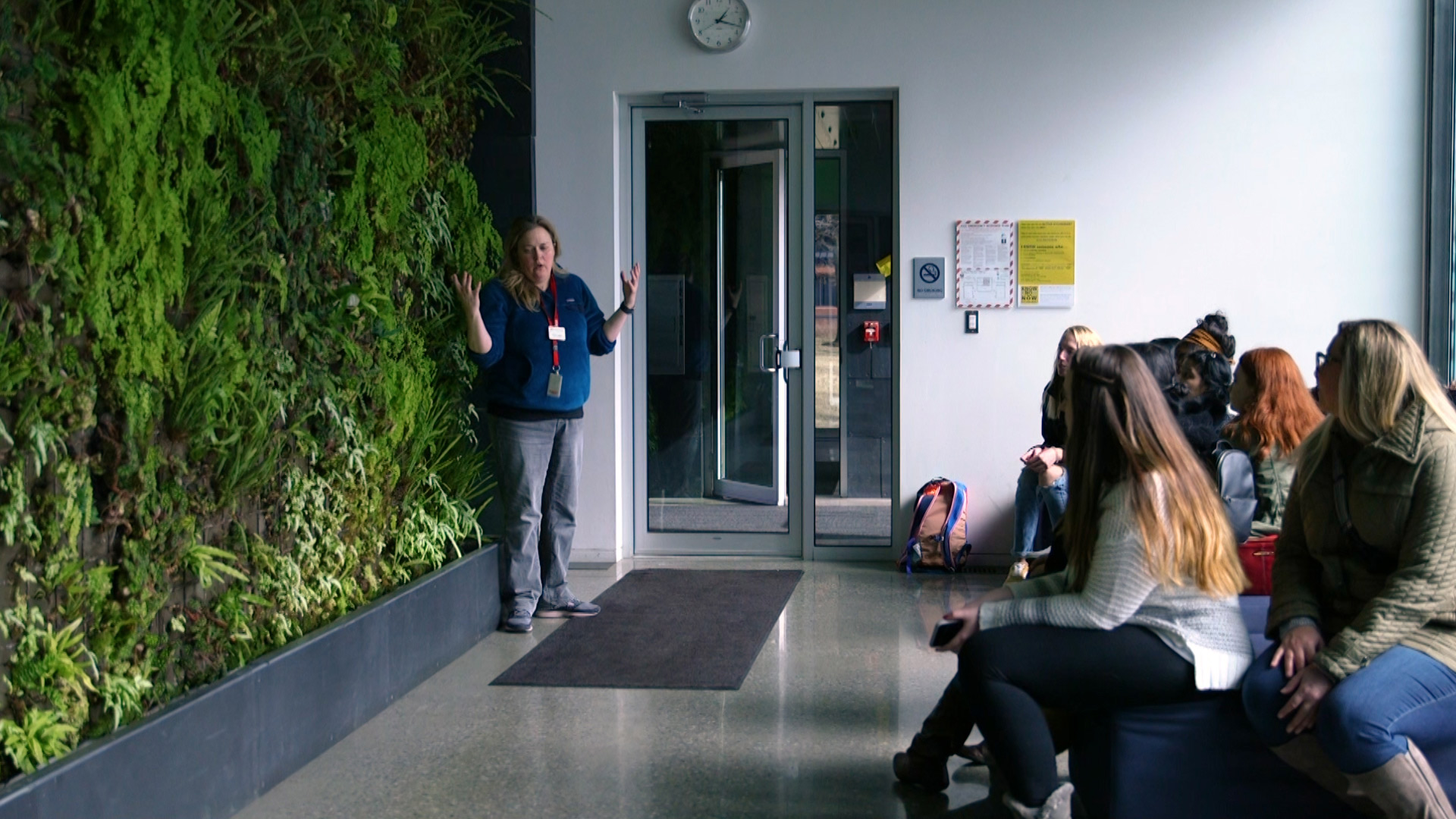 Faculty lecturing in front of the living wall in Galileo's Pavilion