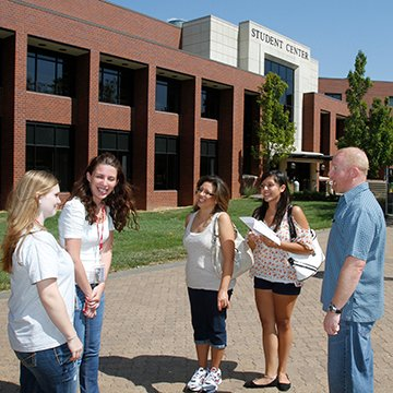 A prospective student and her parents listen as two student ambassadors lead a campus tour.