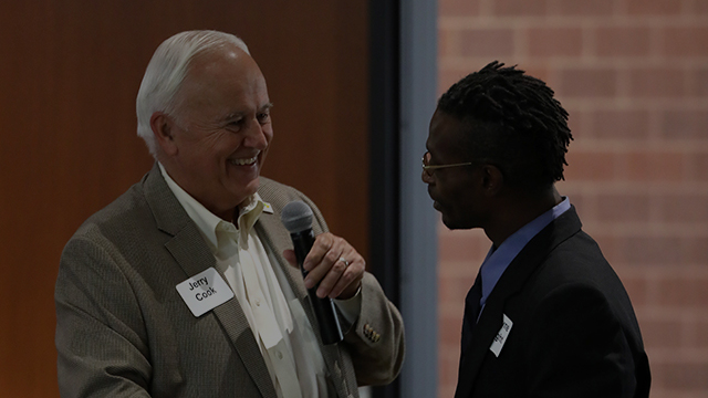 Dr. Jerry Cook congratulates a scholarship recipient at a luncheon.
