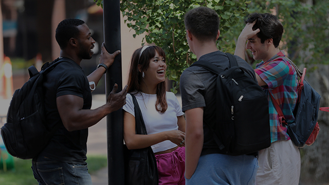 A group of four students chat in Fountain Square