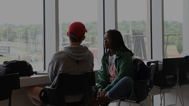 Two students sit by the windows in the student center