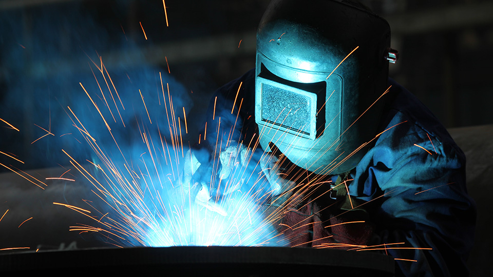 A person wearing a welding helmet makes sparks while welding.