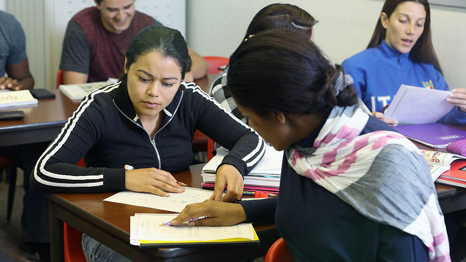 ESL students working with an instructor in a classroom