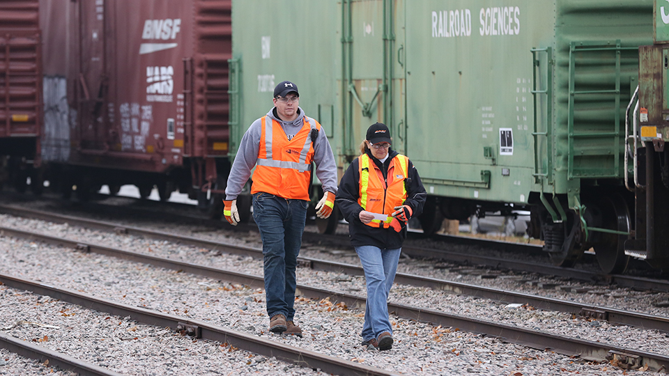Two National Academy of Railroad Science students walking between the rails of a track in the simulated rail yard on the JCCC campus.