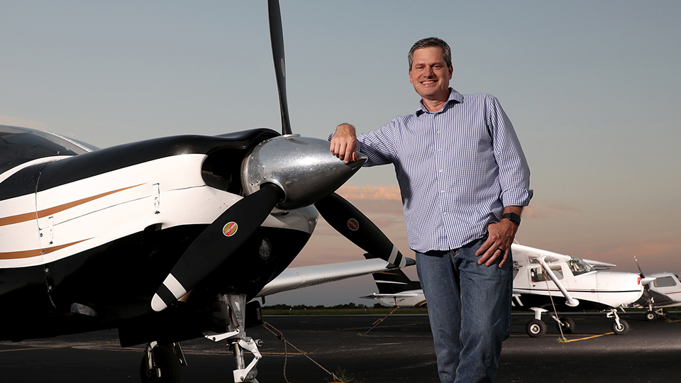 Steven Taylor poses against the propeller of a single-engine airplane