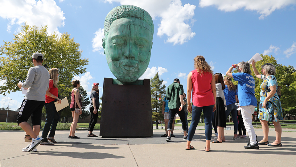 People surround a large sculpture of Charlie Parker's head near 18th and Vine streets.