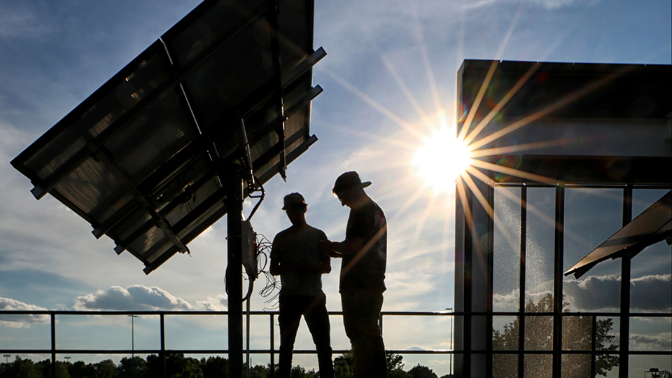 Two students examine solar panels outside CTEC