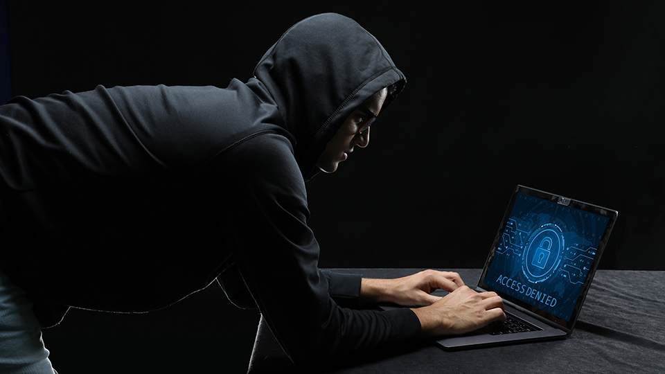 Man in a dark hoodie trying to hack into a laptop