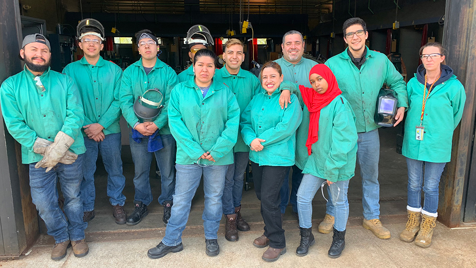Dressed in identical green protective jackets and steel-toed boots, seven male welding students and their male instructor stand in a line behind three female students.