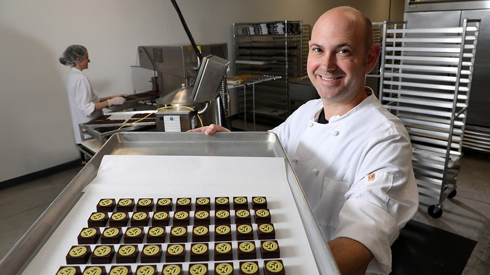 Christopher Elbow Chocolate's Director of Production, Ethan Taylor, shows off customized JCCC 50th Anniversary chocolates.