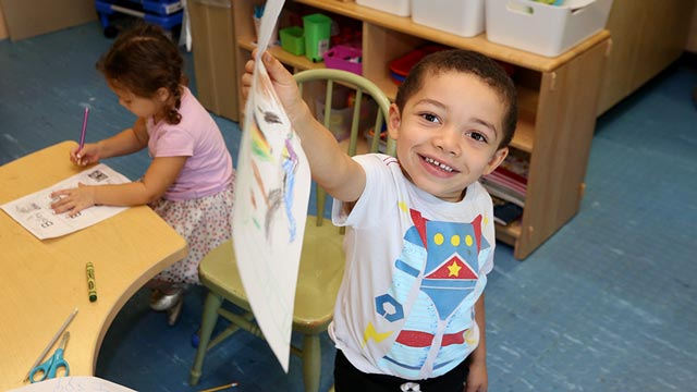Young boy showing off his drawing at the Hiersteiner Child Development Center