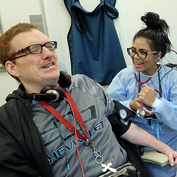 Dental Hygiene student Allie Vasquez laughing with patient James McClum