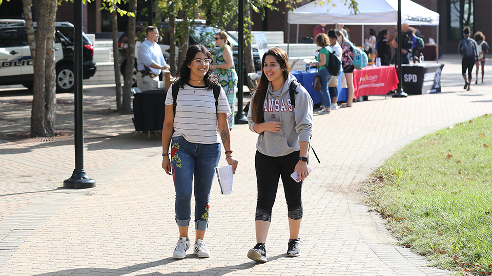 Two female students walking in front of the COM building during Cav Craze
