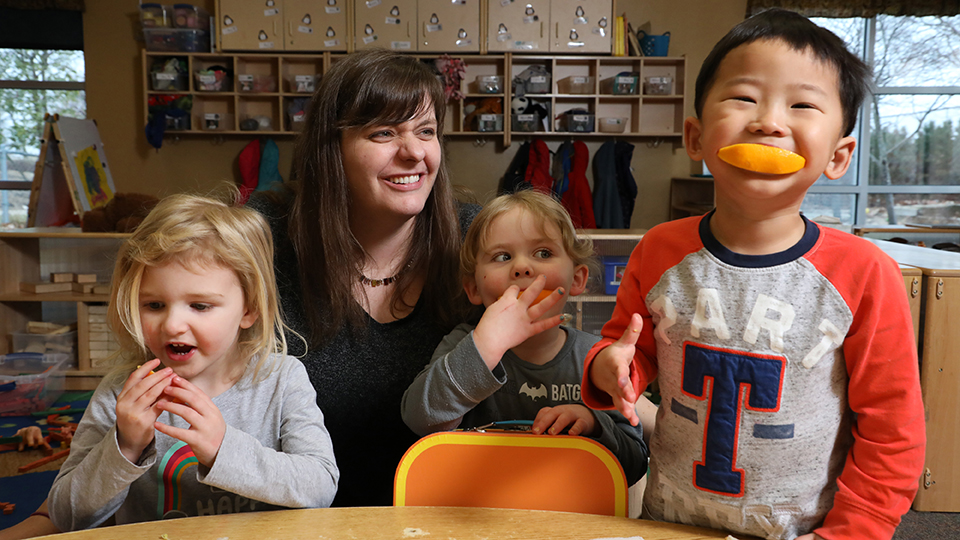 Jennie Brockhoff reacts to the silliness of orange slice smiles during snack time with her childcare kids.