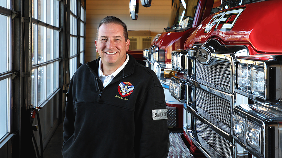 Overland Park Battalion Fire Chief Brian Redelsheimer stands in front of fire trucks.