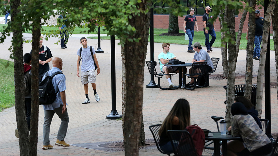 Students walking under the tree in Fountain Square on the JCCC campus