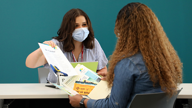 Success advocate wearing a mask helps a student at the Welcome Desk
