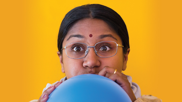 Promotional photo of Mrs. Krishnan blowing up a balloon.
