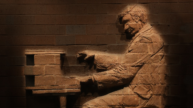 A sculpture of a piano player as seen in the wall of Yardley Hall