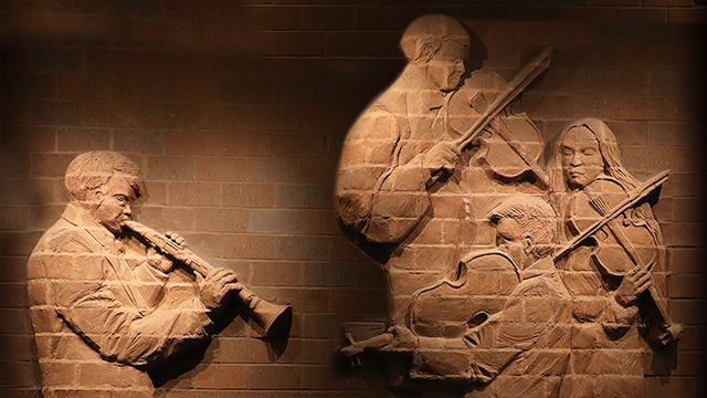 A brick relief mural of musicians.