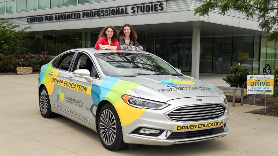 Two JCCC students posing with a car wrapped with the JCCC logo