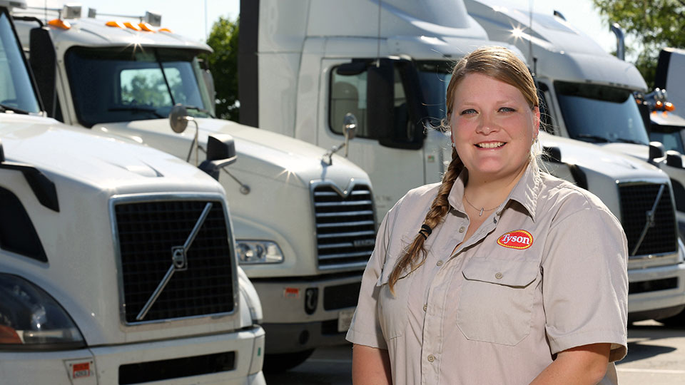 Alison Smith standing in front of a line of semis