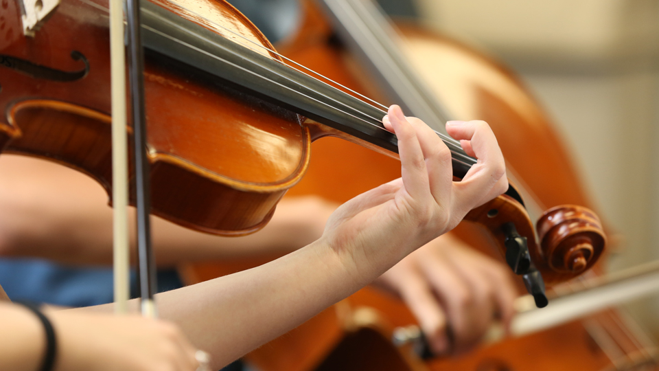 Close up photo of someone playing a violin. Only he hands are shown.
