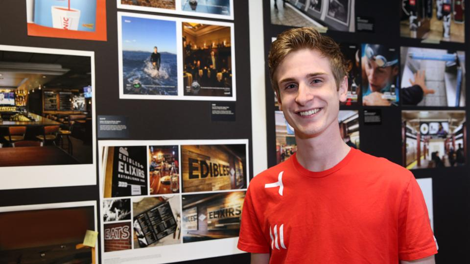 Brend Burford posing in front of graphic design projects