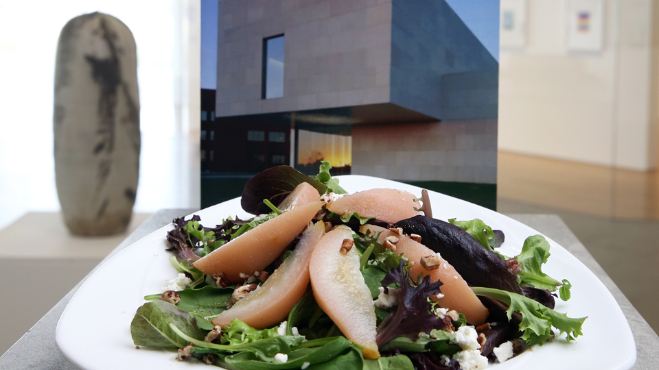 Salad with pears and greens on a triangular plate with the exterior of the Nerman Museum in the background