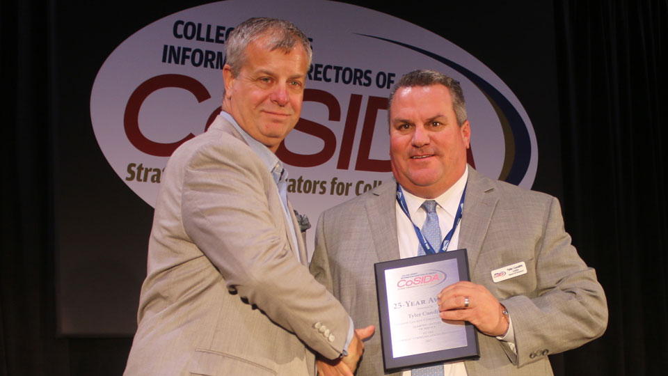 At a recent convention in Orlando, CoSIDA president Andy Seeley (left) presented the organization's 25-year award to Tyler Cundith, Johnson County Community College sports information director. Contributed photo.