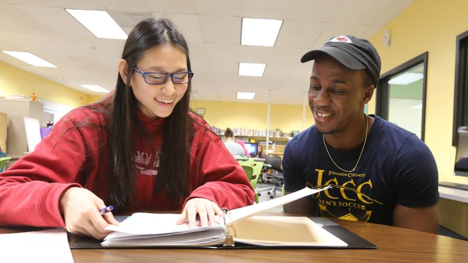 Two smiling students studying together in a resource center