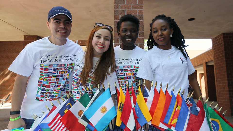 Students in the International Club posing by flags of various countries