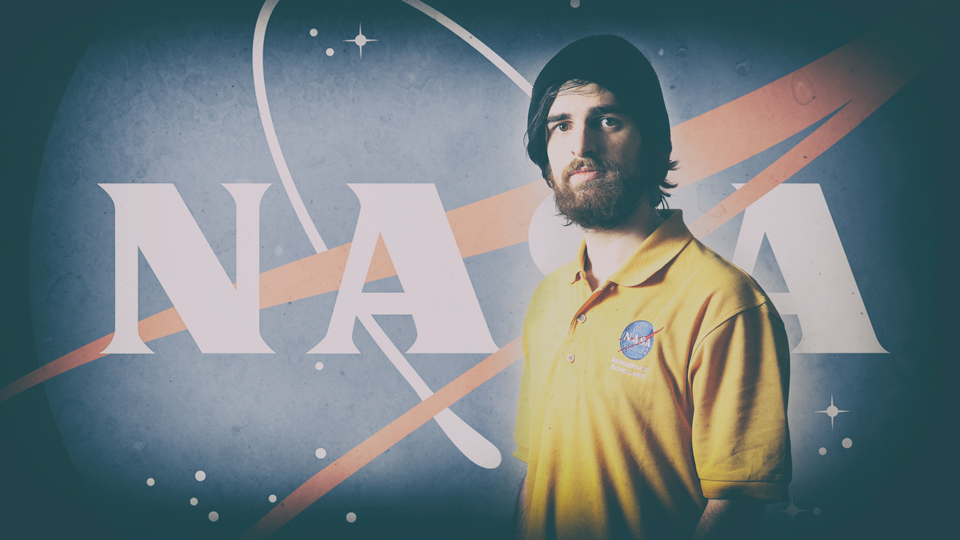 Isaac Jambor standing in front of a backdrop of the NASA logo