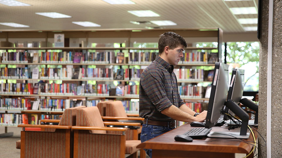 A man uses a computer in the JCCC library