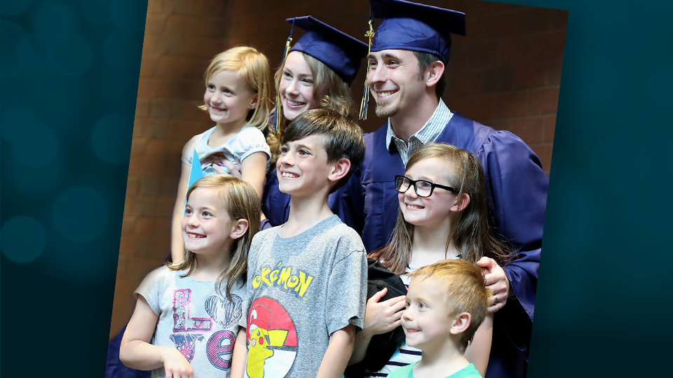 Cody Davidson posing in cap and gown with his wife and five children