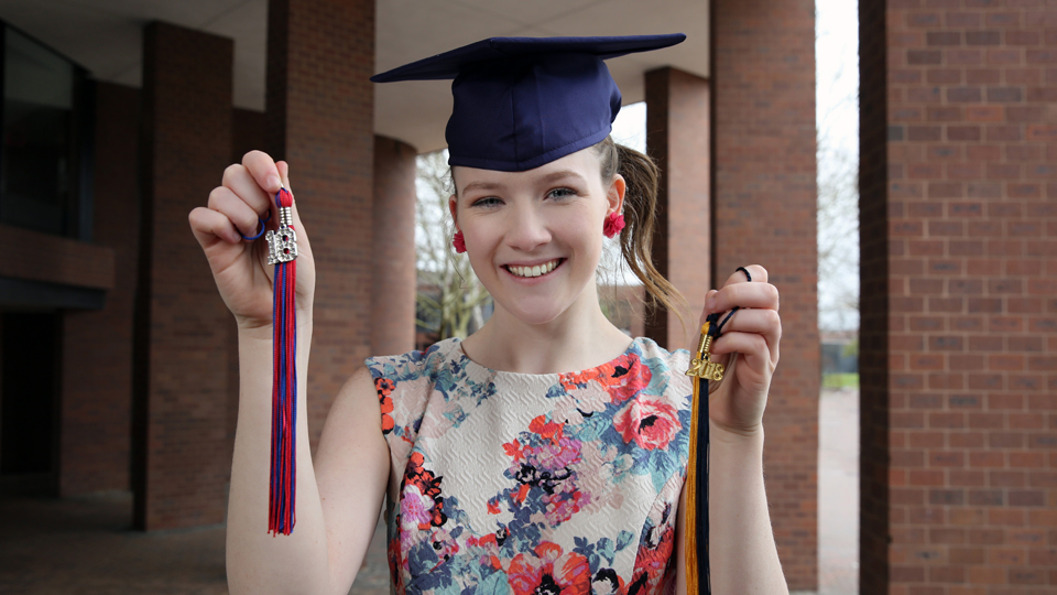 Grace Palcic wearing a graduation cap and holding tassels from two different schools