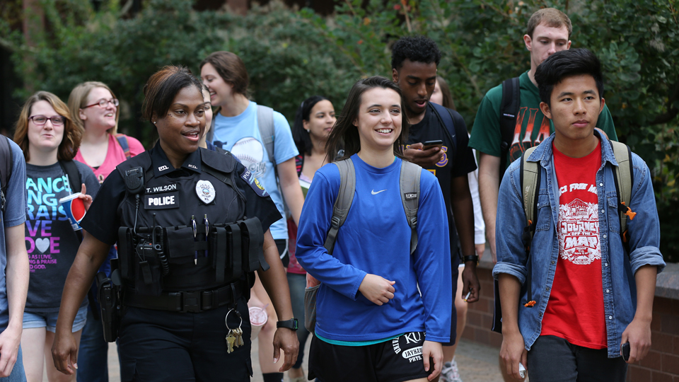 JCCC police officer walking and talking with a group of students