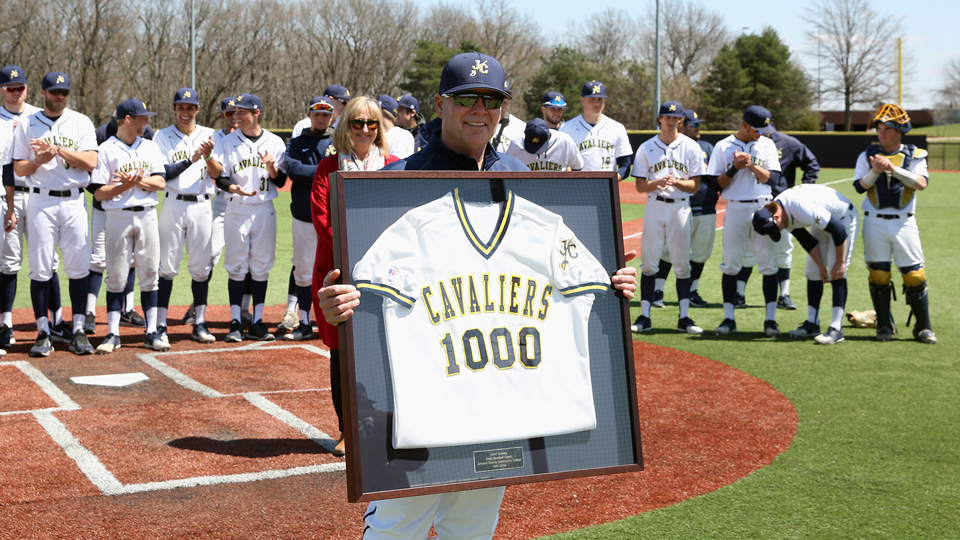 Coach Kent Shelley posing with a framed JCCC baseball jersey with the number 1,000 on it.