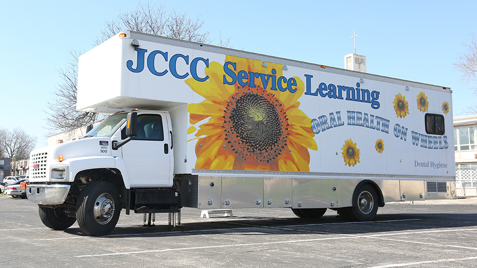 The Oral Health on Wheels van with an image of a sunflower on the side and the words JCCC service learning oral health on wheels