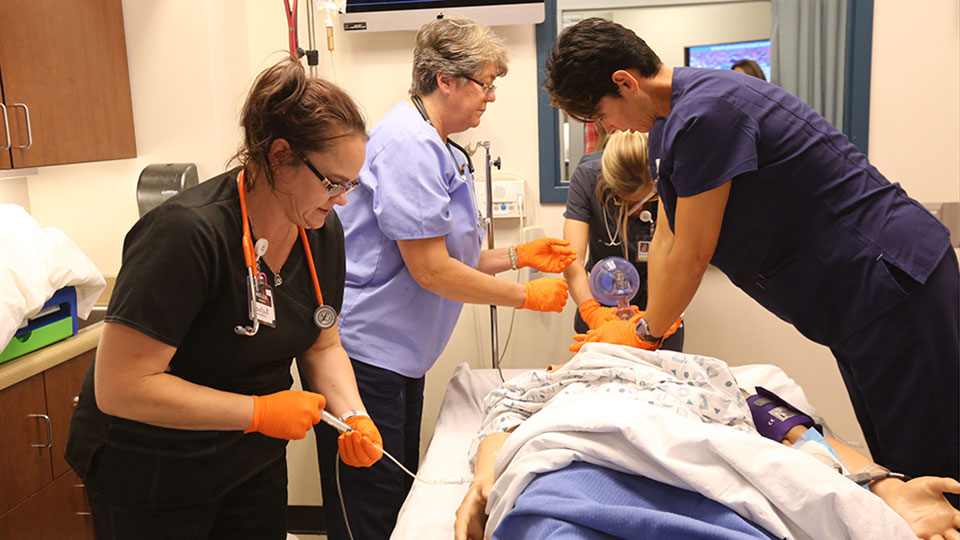 Three students practices aspects of healthcare on a simulation mannequin while an instructor looks on.